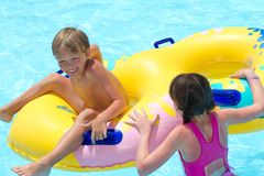 Kids playing with a raft. A pair of kids playing in the swimming pool with a yellow raft Royalty Free Stock Photos