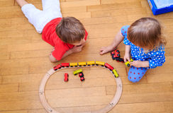 Kids playing with railroad and trains indoor Royalty Free Stock Images