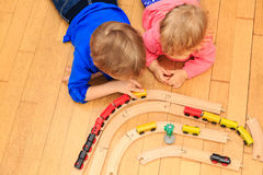Kids playing with railroad and trains indoor Royalty Free Stock Photos