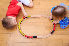 Kids playing with railroad and trains indoor Royalty Free Stock Photo