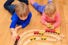 Kids playing with railroad and trains indoor Royalty Free Stock Image