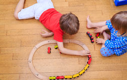 Kids playing with railroad and trains indoor Stock Photo