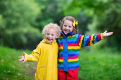 Kids playing in the rain. Little boy and girl play in rainy summer park. Children with colorful rainbow jacket and waterproof boots jump in puddle and mud in the Royalty Free Stock Photos