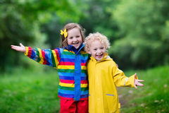Kids playing in the rain. Little boy and girl play in rainy summer park. Children with colorful rainbow jacket and waterproof boots jump in puddle and mud in the Stock Photography
