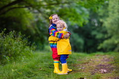 Kids playing in the rain. Little boy and girl play in rainy summer park. Children with colorful rainbow jacket and waterproof boots jump in puddle and mud in the Royalty Free Stock Image