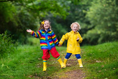 Kids playing in the rain. Little boy and girl play in rainy summer park. Children with colorful rainbow jacket and waterproof boots jump in puddle and mud in the Stock Photos