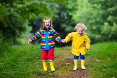 Kids playing in the rain. Little boy and girl play in rainy summer park. Children with colorful rainbow jacket and waterproof boots jump in puddle and mud in the Stock Images