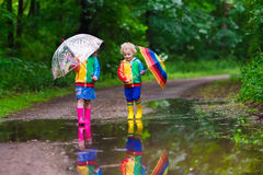 Kids playing in the rain. Little boy and girl play in rainy summer park. Children with colorful rainbow umbrella, waterproof boots jump in puddle and mud in the Stock Photos