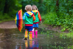 Kids playing in the rain royalty free stock photos