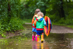 Kids playing in the rain with umbrella. Little boy and girl play in rainy summer park. Children with colorful rainbow umbrella, waterproof boots jump in puddle Royalty Free Stock Photo
