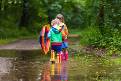Kids playing in the rain with umbrella stock images