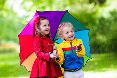 Kids playing in the rain under colorful umbrella. Little boy and girl play in rainy summer park. Children with colorful rainbow umbrella, waterproof jacket and Stock Photography