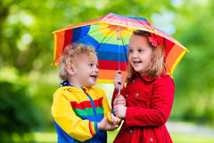 Kids playing in the rain under colorful umbrella. Little boy and girl play in rainy summer park. Children with colorful rainbow umbrella, waterproof jacket and Royalty Free Stock Photo