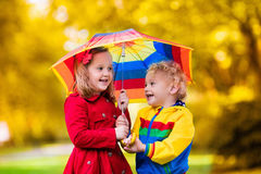 Kids playing in the rain under colorful umbrella. Little boy and girl play in rainy summer park. Children with colorful rainbow umbrella, waterproof jacket and Stock Image