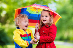 Kids playing in the rain under colorful umbrella. Little boy and girl play in rainy summer park. Children with colorful rainbow umbrella, waterproof jacket and Stock Images