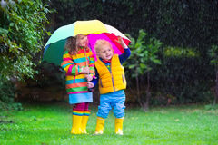 Kids playing in the rain under colorful umbrella. Little girl and boy with colorful umbrella playing in the rain. Kids play outdoor by rainy weather in fall Royalty Free Stock Photo