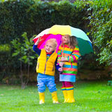 Kids playing in the rain under colorful umbrella. Little girl and boy with colorful umbrella playing in the rain. Kids play outdoor by rainy weather in fall Royalty Free Stock Images