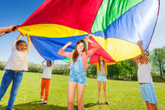 Kids playing with rainbow parachute in the park. Joyful kids playing with rainbow parachute, standing under it`s big canopy in the park royalty free stock images