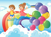 Kids playing with the rainbow in the sky Royalty Free Stock Photos
