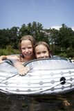 Kids playing in the river. Two young ls in inflatable toy playing in the river in summer royalty free stock photos