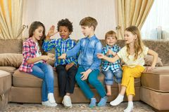 Kids playing rock paper scissors. Group of children indoor. Family competition games Royalty Free Stock Photos