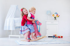 Kids playing with rocking horse Royalty Free Stock Image