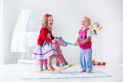 Kids playing with rocking horse Royalty Free Stock Photos