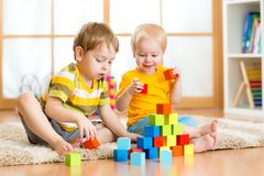 Kids playing in the room. Kids playing block toys in playroom at nursery Royalty Free Stock Photo
