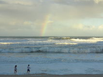 Kids at beach by stormy sea with rainbow Stock Image