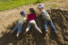 Kids playing in the sand. Kids playing in the garden in a big sandheap Royalty Free Stock Images