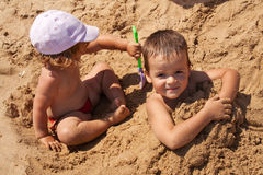Kids playing in sand. Young kids playing in golden sand - closeup Stock Photos