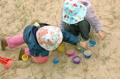 Kids playing with sand. Two little girl playing with sand outdoors Royalty Free Stock Photography