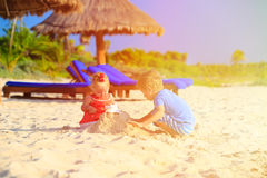Kids playing with sand on beach. Kids playing with sand on summer tropical beach Royalty Free Stock Photos