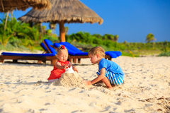 Kids playing with sand on beach. Kids playing with sand on summer tropical beach Stock Photography