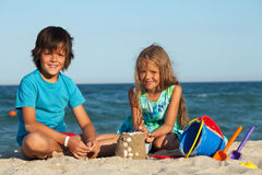 Kids playing in the sand. Building castles together on the beach Royalty Free Stock Photo