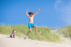 Kids playing in sand dunes. Happy laughing kids, school age boy and funny culy toddler girl, brother and sister, playing on a beach,jumping in sand dunes Stock Photos