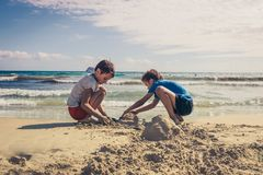 Kids play with sand on sea beach Stock Photography