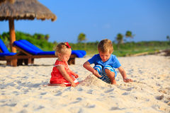 Kids playing with sand on summer beach. Kids playing with sand on summer tropical beach Royalty Free Stock Photos