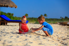 Kids playing with sand on summer beach. Kids playing with sand on summer tropical beach Royalty Free Stock Image