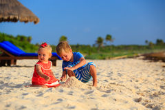 Kids playing with sand on summer beach Stock Images