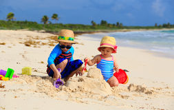Kids playing with sand on summer beach. Kids playing with sand on summer tropical beach Royalty Free Stock Photo