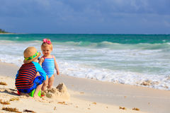 Kids playing with sand on tropical beach. Little boy and toddler girl playing with sand on tropical beach Royalty Free Stock Photo