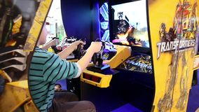Kids are playing in SEGA Transformers Video Arcade Game in Game center. MOSCOW, RUSSIA - APRIL 16, 2015: Kids are playing in SEGA Transformers Video Arcade Game stock video