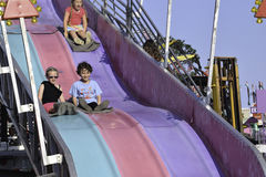Kids Playing on Slide. Wall Township, NJ USA June 29, 2014. Kids riding down a large colorful sliding board on fairgrounds in Wall Township, NJ. Editorial Use Royalty Free Stock Photography