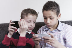 Kids playing on smartphone. Two boys playing games on smartphone. Having fun. Concept of modern family Royalty Free Stock Photo