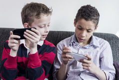 Kids playing on smartphone. Two boys playing games on smartphone. Having fun. Concept of modern family Stock Photos