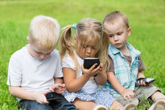 Kids playing on smartphones sitting on the grass Royalty Free Stock Photos