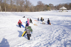 Kids playing in snow. Kids walk up snow after sleigh riding in fresh snow near Lexington, MA, New England, USA Stock Photos