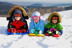 Kids playing in snow. Three kids playing in a snowy hilly landscape Royalty Free Stock Photo
