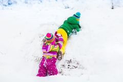 Kids playing in snow. Children play outdoors in winter snowfall. Royalty Free Stock Image